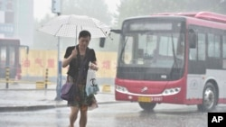 2016年7月19日,河北省石家庄一位行人走在大雨中。