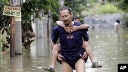 Wani mutum a kasar Indonesia yake goye da dansa cikin ambaliyar ruwa da girgizar kasa da mummunar igiyar ruwa da kasar take fama da shi.