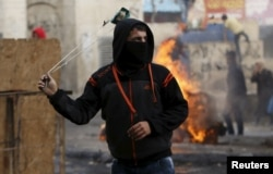 FILE - A Palestinian protester uses a sling to hurl stones at Israeli troops in Hebron, West Bank, Nov. 5, 2015.