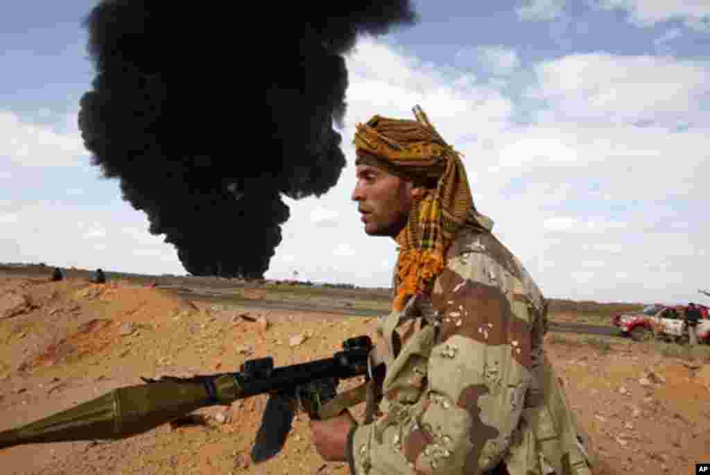 A rebel walks with his rocket propelled grenade launcher during clashes with pro-Gadhafi forces between Ras Lanuf and Bin Jawad, Mar 9, 2011