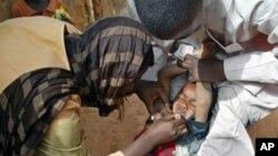 Volunteers administer a polio vaccine to a child in Kaduna, Nigeria.