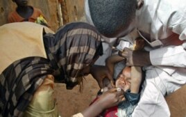 Volunteers administer polio vaccine to a child in Kaduna, Nigeria.