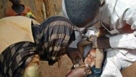Des volontaires vaccinant un enfant à Kaduna, au Nigeria.
