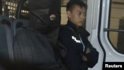 涉嫌在美国加州杀死自己两名侄子的石德云在香港被捕后坐在警车里,在警察旁边(2016年1月25日)