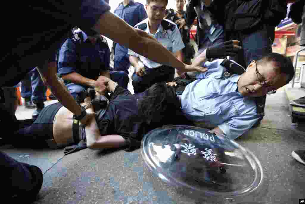 A pro-democracy protester is arrested by riot police in the Mong Kok district of Hong Kong, early Friday, Oct. 17, 2014.