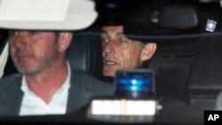 Cựu Tổng thống Pháp Nicolas Sarkozy (phải) rời khỏi đồn cảnh sát, nơi ông bị giam tại Nanterre, ngoại ô Paris, ngày 21/3/2018.