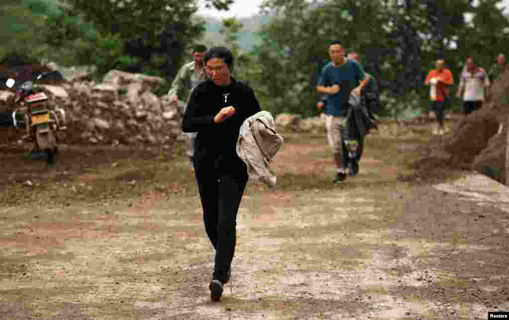 People run past a hillside alley which is at risk of landslide after an earthquake hit Ludian county of Zhaotong, Yunnan province.