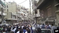 Mourners attend the funerals of protesters killed in earlier clashes in the Syrian city of Homs, April 18, 2011