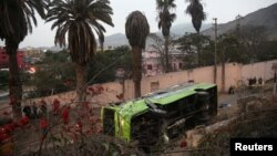 Police officers, firemen and rescue personnel inspect a double-decker tourist bus after it crashed near the tourist site of San Cristobal in Lima, Peru, July 9, 2017.