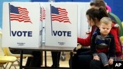 Une Américaine tient son enfant alors qu'elle remplit son bulletin de vote à Alexandria, Virginie, le 7 novembre 2017.