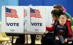 7일 미국 버지니아주 알렉산드리아시의 투표소에서 한 여성이 아이를 안고 투표하고 있다.