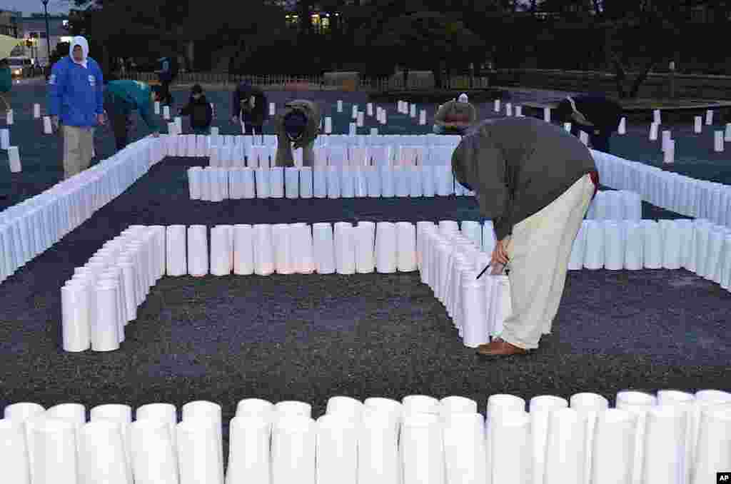 Lighting candles in Matsushima to remember those killed, March 9, 2012. (VOA - S. L. Herman)