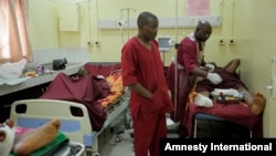 Paramedics treat a victim of Monday's explosion at Asokoro hospital in Abuja, Nigeria, April 15, 2014.
