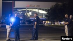Officials stand by the scene outside the movie theater where a man opened fire on film-goers in Lafayette, Louisiana, July 23, 2015.