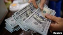 Một nhân viên điếm các tờ tiền đô la Mỹ tại một chi nhánh ngân hàng ở Hà Nội, Việt Nam. Lượng kiều hối về Việt Nam đạt kỷ lục trong năm nay với gần 16,7 tỷ USD, theo Ngân hàng Thế giới.