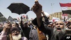 People attend Friday prayers in Tahrir Square in Cairo. Tens of thousands of Egyptians demanded on Friday that their military rulers stick to a pledge to hand over power by mid-year after a row over who can run in the presidential election raised doubts a