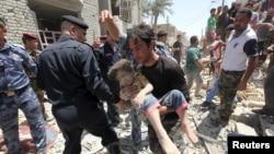 Мужчина несет раненого ребенка извлеченного из под завала. Багдад 6 июля 2015 года.