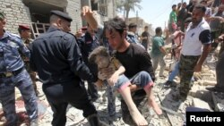 A man carries an injured child found in the rubble after an Iraqi Sukhoi jet accidentally dropped a bomb in Ni'iriya, an eastern neighborhood in Baghdad, July 6, 2015..