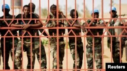FILE - United Nations peacekeepers from Senegal peer from behind a gate in Gao, Mali, during a protest against sending them to the northern rebel-held town of Kidal, July 5, 2013.