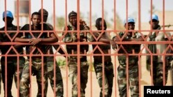 FILE - U. N. peacekeepers peer from behind a gate in Gao during a protest against sending them to the northern rebel-held town of Kidal, Mali, where attempts to reach an accord between the government and rebel movements have proven difficult.