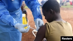 FILE - A Congolese health worker administers Ebola vaccine to a boy who had contact with an Ebola sufferer in the village of Mangina in North Kivu province of the Democratic Republic of Congo, Aug.18, 2018.