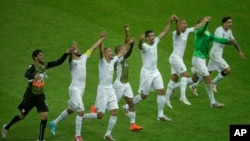 Members of the Algerian soccer team celebrate on the pitch after beating South Korea 4-2 on June 22, 2014.