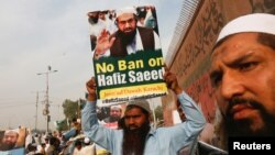 FILE - A supporter of Islamic charity organization Jamaat-ud-Dawa (JuD) carries a sign with others as they listen to the speech of leaders (unseen) to condemn the house arrest of Hafiz Saeed, chief of (JuD) during a protest demonstration in Karachi, Pakistan, Feb. 3, 2017.
