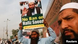 FILE - A supporter of Islamic charity organization Jamaat-ud-Dawa (JuD), carries a sign with others as they listen the speech of leaders (unseen) to condemn the house arrest of Hafiz Muhammad Saeed, chief of (JuD), during a protest demonstration in Karachi, Pakistan, Feb. 3, 2017.
