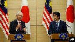 Perdana Menteri Malaysia Najib Razak (kiri) dan Perdana Menteri Jepang Shinzo Abe dalam konferensi pers bersama di Tokyo (25/5). (AP/Issei Kato. pool)