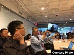 """哈佛大学""""改革开放40年:挑战和机遇""""系列研讨,无法到场的天则经济研究所所长盛洪教授的视频发言,学者吴思举着电脑播放视频(盛洪推特照片)"""