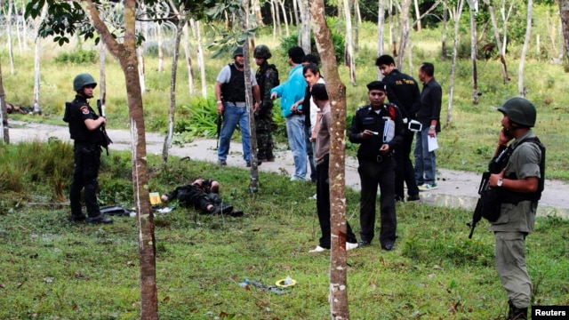 Security personnel investigate around bodies of insurgents at the site of an attack on an army base in the troubled southern province of Narathiwat, February 13, 2013.