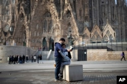 People take a selfie outside the Sagrada Familia basilica in Barcelona, Spain, Friday, March 13, 2020. The basilica closed its doors to visitors and suspend construction from Friday March 13 to prevent the spread of the new COVID-19 coronavirus