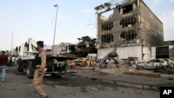 Security forces inspect the site of a car bomb explosion in the largely Shi'ite eastern neighborhood of Talibiyah in Baghdad, Iraq, Oct. 16, 2014.