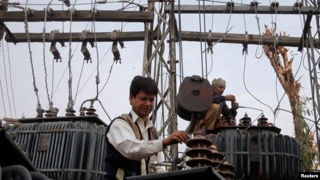 Công nhân thay thế máy biến áp điện bên ngoài một khu phố ở Lahore.