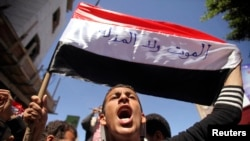 "An anti-Houthi protester shouts slogan as he holds a Yemeni flag on which the words, ""Neither death nor humiliation"" during a demonstration in the southwestern city of Taiz, Feb. 9, 2015."