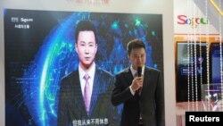 在中国乌镇国际互联网大会上,新华社新闻主播邱浩站在以他为原型的人工智能技术合成的新闻主播播放新闻的屏幕前。(2018年11月7日)
