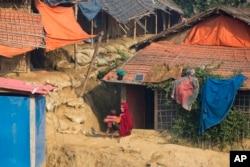 ស្ត្រីជនភៀសខ្លួនរ៉ូហ៊ីងយ៉ាកាន់សាសនាឥស្លាមជាមួយកូនរបស់គាត់នៅខាងក្រៅកន្លែងស្នាក់នៅក្នុងជំរំ Balukhali ស្រុក Cox's Bazar ប្រទេសបង់ក្លាដែស កាលពីខែវិច្ឆិកា ២០១៨។