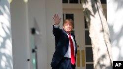 美国总统特朗普2018年10月1日在白宫玫瑰园附近的柱廊向媒体记者挥手致意。