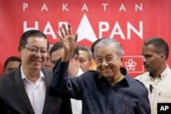 FILE - Malaysia's Prime Minister Mahathir Mohamad, center, waves next to newly appointed Finance Minister Lim Guan Eng, left, after a press conference to announce his cabinet members in Petaling Jaya, May 12, 2018.
