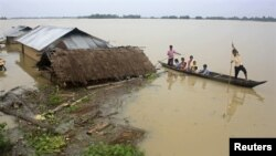 Flood-affected local residents move to safer places on a boat next to their damaged huts after heavy rains at Jajimukh village in the northeastern Indian state of Assam June 27, 2012. Incessant heavy rains in northeast India have caused massive flooding a