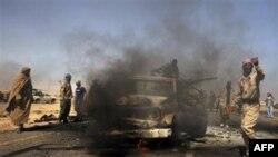 Libijski pobunjenici pored vozila Gadafijevih snaga za koje tvrde da je uništeno u vazdušnom udaru NATO-a.