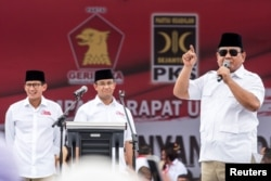 FILE - Gerindra party Chairman Prabowo Subianto, right, talks to supporters during a campaign for Anies Baswedan, center, a candidate in the running to lead the Indonesian capital, Jakarta, in Jakarta, Indonesia Feb. 5, 2017.