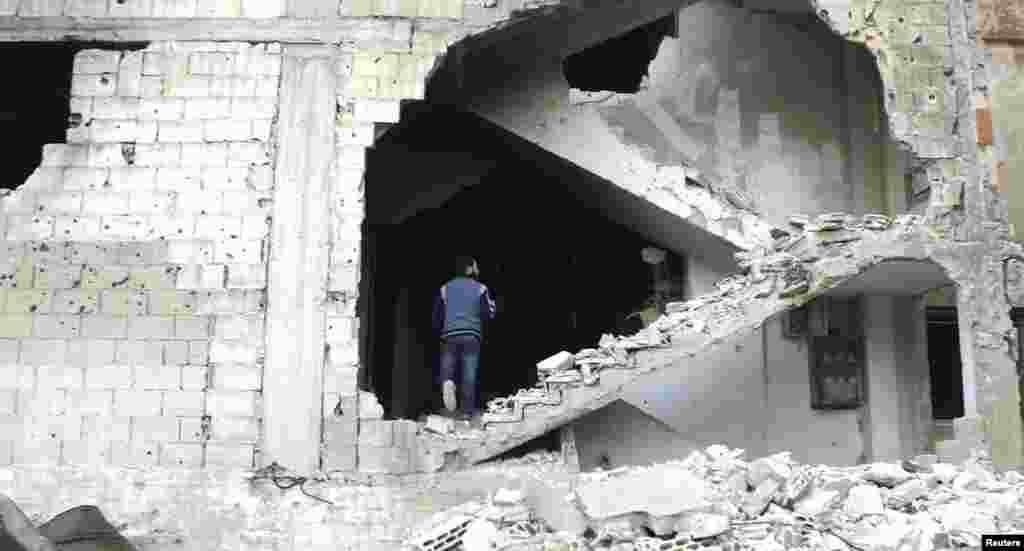 A man is seen on a damaged staircase in Homs, Syria.