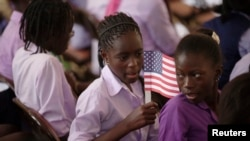 Une élève tenant un drapeau américain avant l'arrivée de la première dame des Etats-Unis, Michelle Obama, à l'école de filles Martin Luther King, à Dakar, 27 juin 2013.