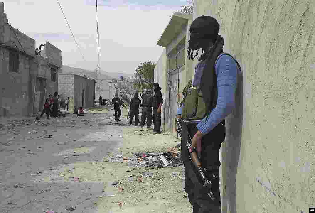 In this Sunday, April 1, 2012 photo, A Free Syrian Army fighter stands guard in a neighborhood in Damascus. (AP)