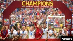 United States goalkeeper Hope Solo (1) hoists the FIFA Women's World Cup trophy as she and her teammates pose with their medals after defeating Japan in the final of the FIFA 2015 Women's World Cup at BC Place Stadium, July 5, 2015.