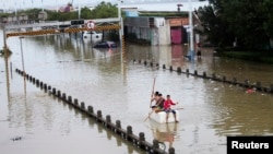 Residents paddle a makeshift raft as they make their way along a flooded street after Typhoon Fitow hit Rui'an, Oct. 7, 2013.