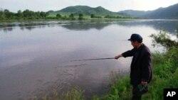 Nông dân Trung Quốc câu cá trên sông Ðồ Môn trong tỉnh Cát Lâm, phía đông bắc Trung Quốc, đối diện là đất nông nghiệp của Bắc Triều Tiên.