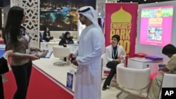 An exhibitor talks to a visitor to The World Halal Travel Summit & Exhibition in Abu Dhabi, United Arab Emirates. Muslim countries in Southeast Asia hope the U.S. travel ban on people from 7 Muslim-majority countries will help them increase tourism.