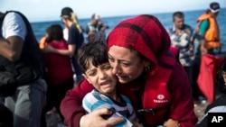 Une Syrienne porte un enfant qu'elle embrace à leur arrivée à l'ile Lesbos, Grèce, venant de la Turquie, 11 septembre 2015.